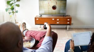 Two people sit on a couch and use a remote to watch TV.