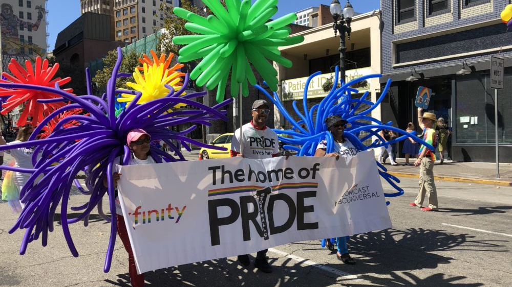 Comcast employees hold a Pride banner as they march in a parade.