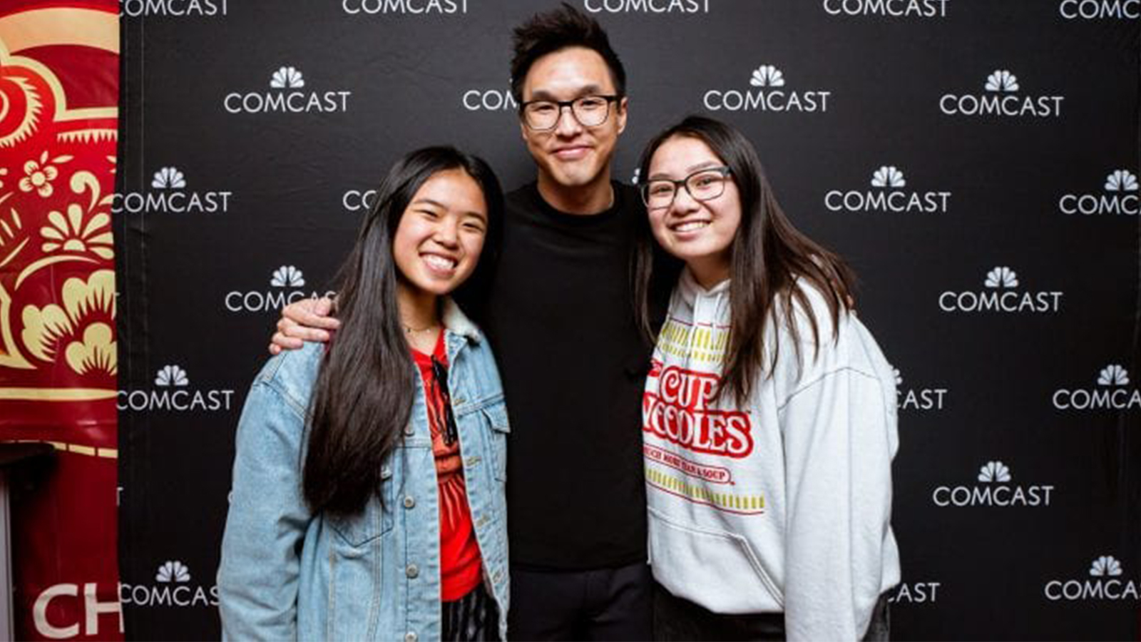 Wesley Chan in front of a Comcast branded backdrop with fans.