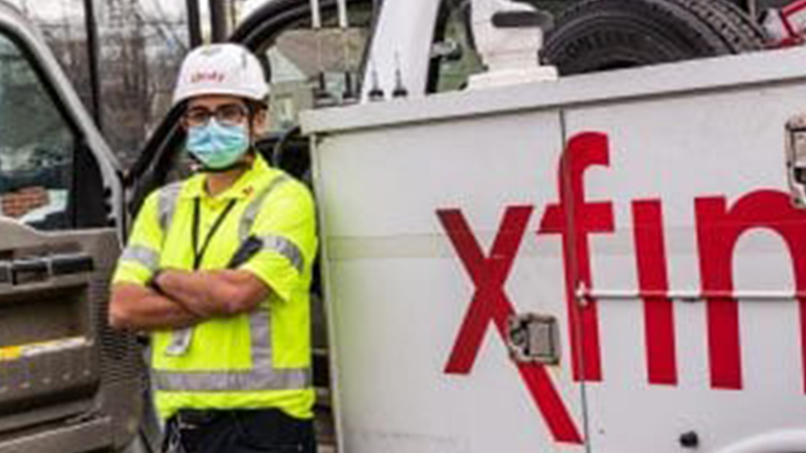 An employee standing in front of an Xfinity truck.