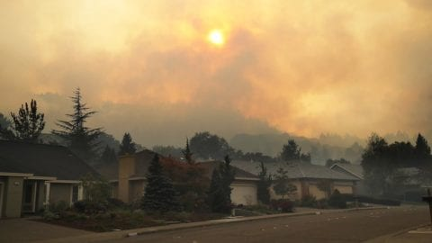 A California neighborhood with clouds of smoke in the sky